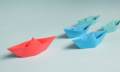 paper boats the red boat leads the blue boats as an example of leadership