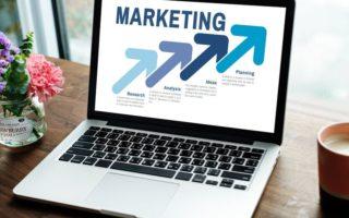 some marketing strategies open laptopn with marketing written on screen