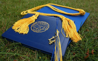 graduate hat in blue with yellow cording political management degree