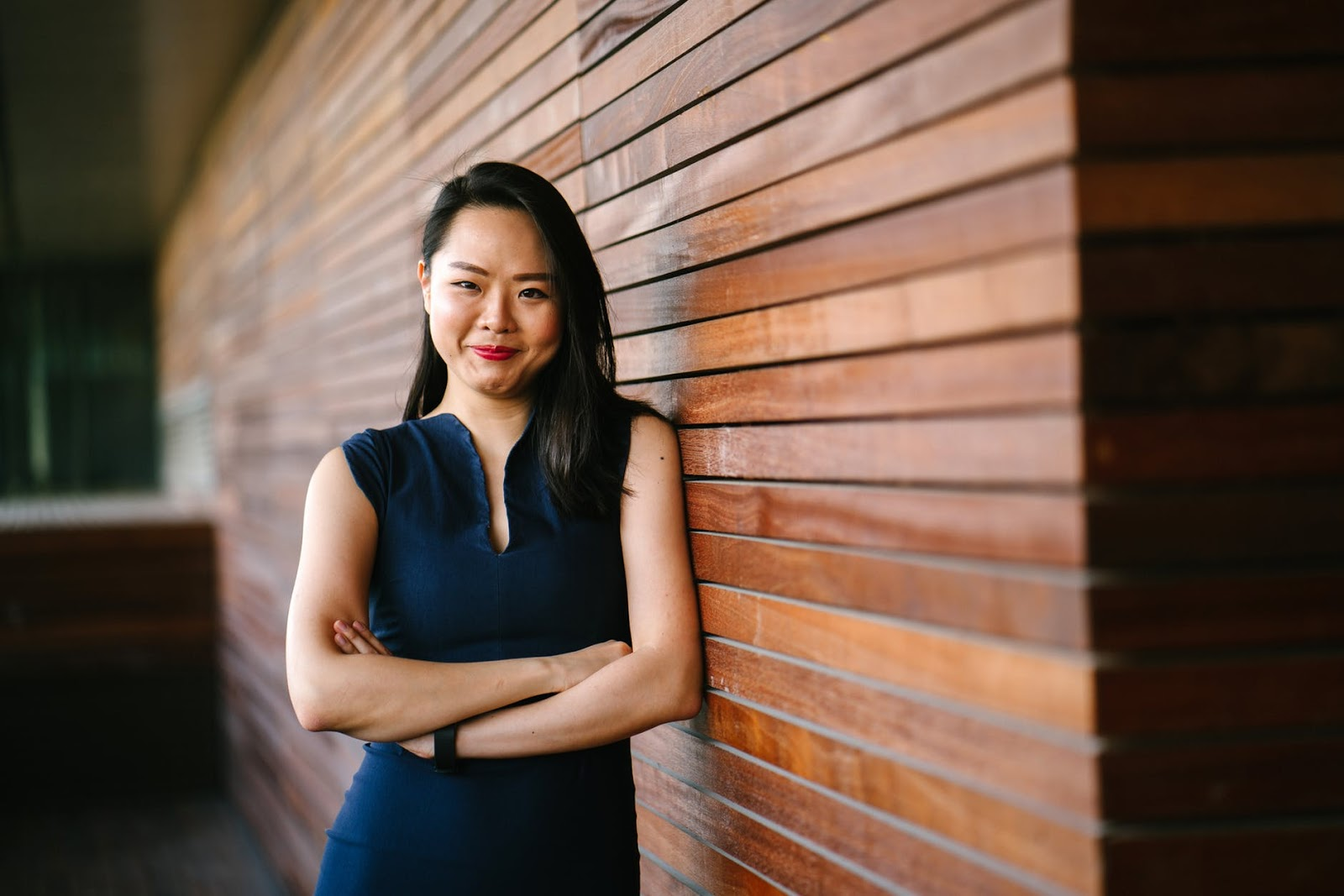 woman in blue dress posing against wooden partition thinking about changing jobs advice