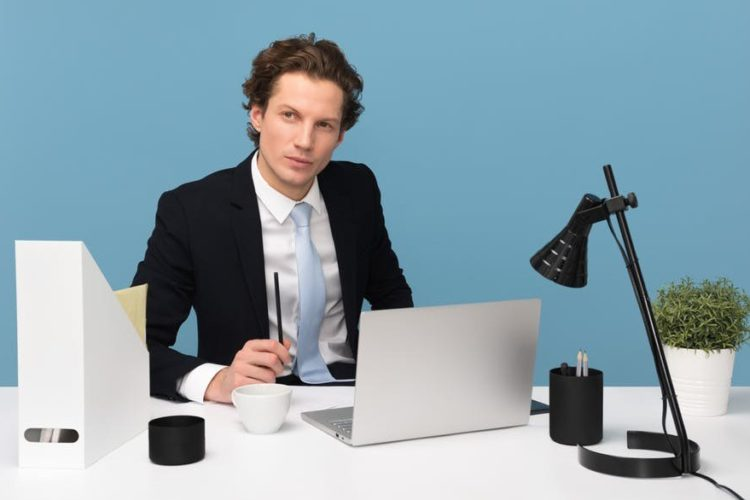business man sitting at his desk with open laptop