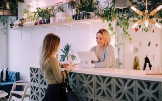 a woman at a cash checkout how to make your business better