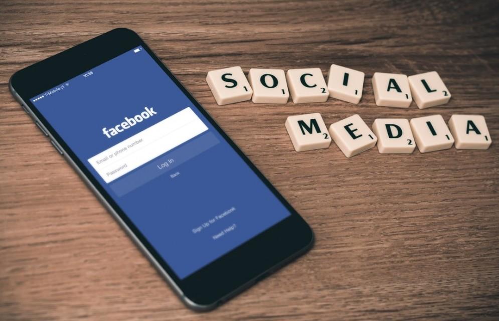 social media on scrabble tiles beside an iphone