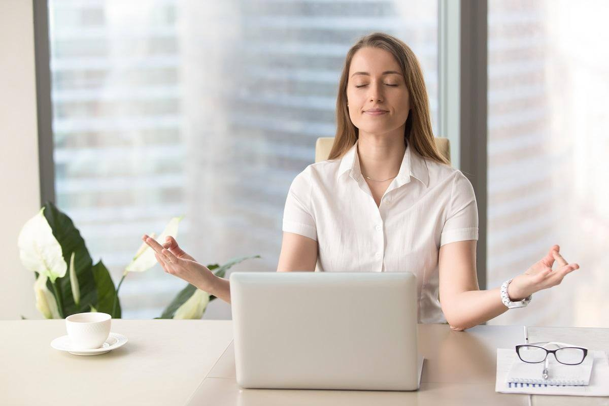woman meditating before a laptop reduce stress immediately