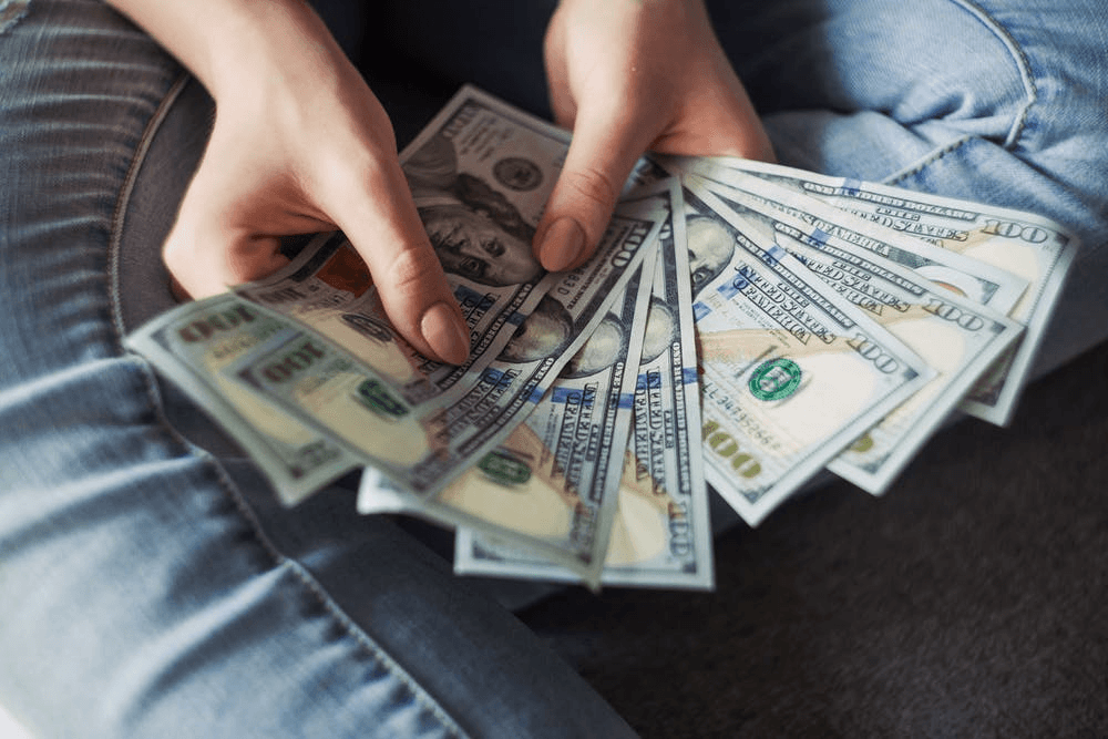 person-holding-100-us-dollar-banknotes- unexpected company expenses to take care of