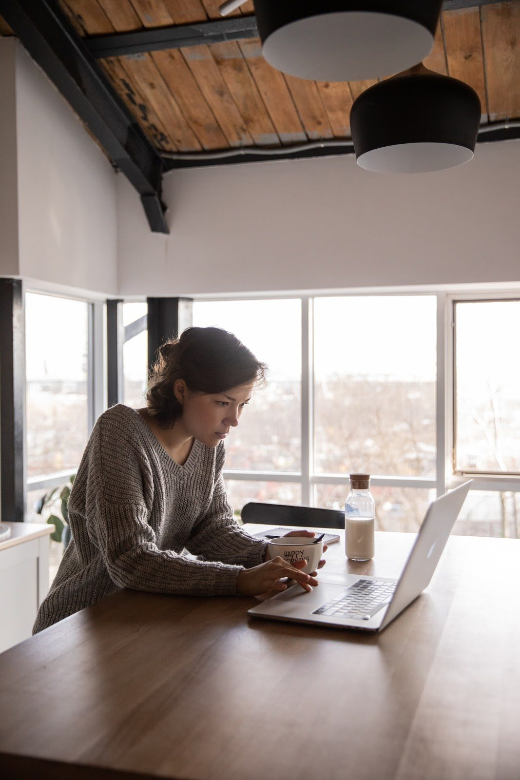 focused-young-woman-using-laptop-in-kitchen-during-breakfast improve your business website planning