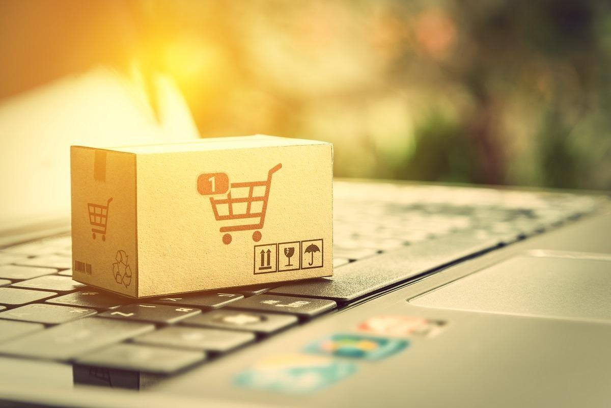 small box with shopping cart icon on laptop keyboard