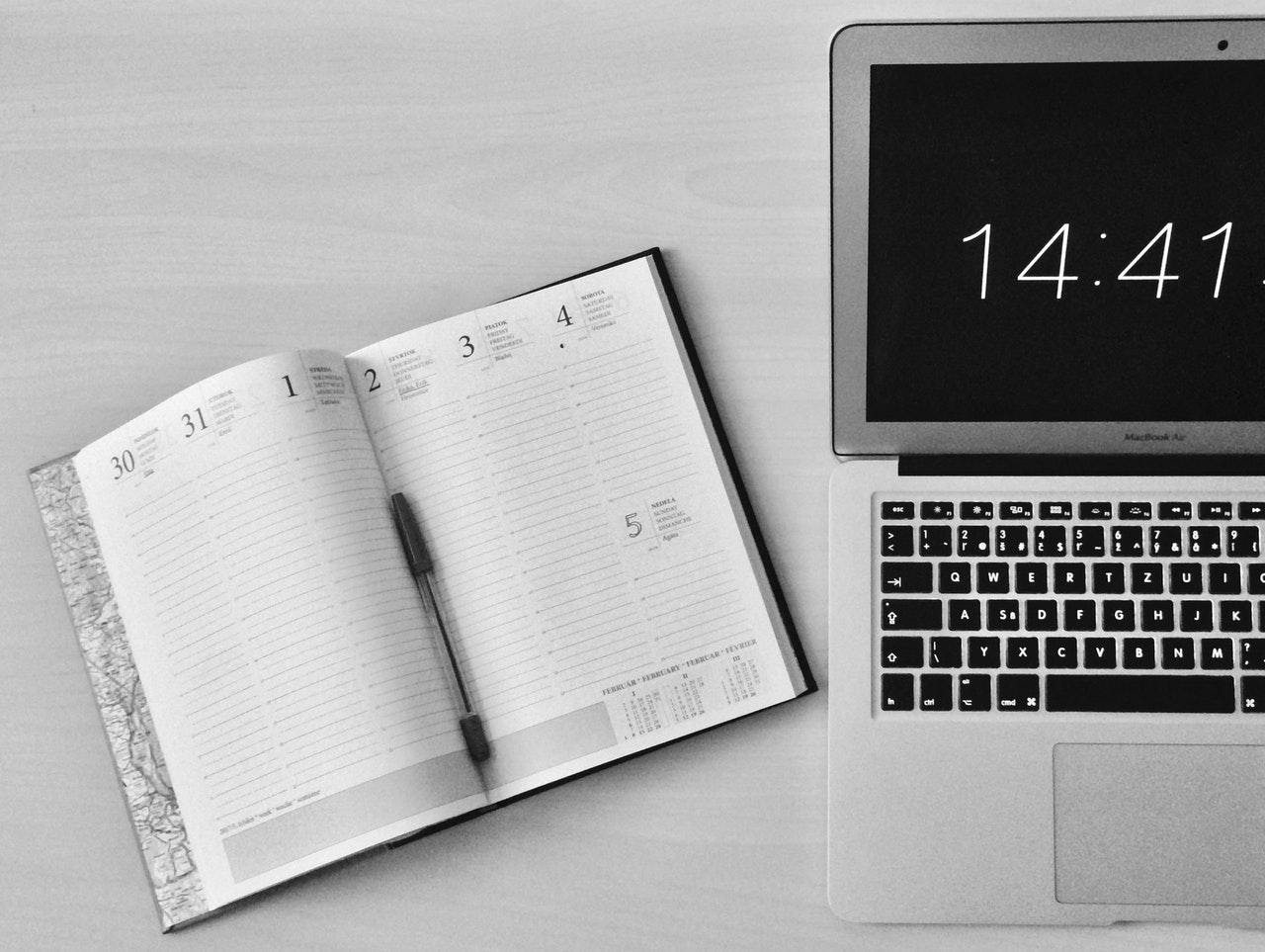 date book beside open laptop with time on screen