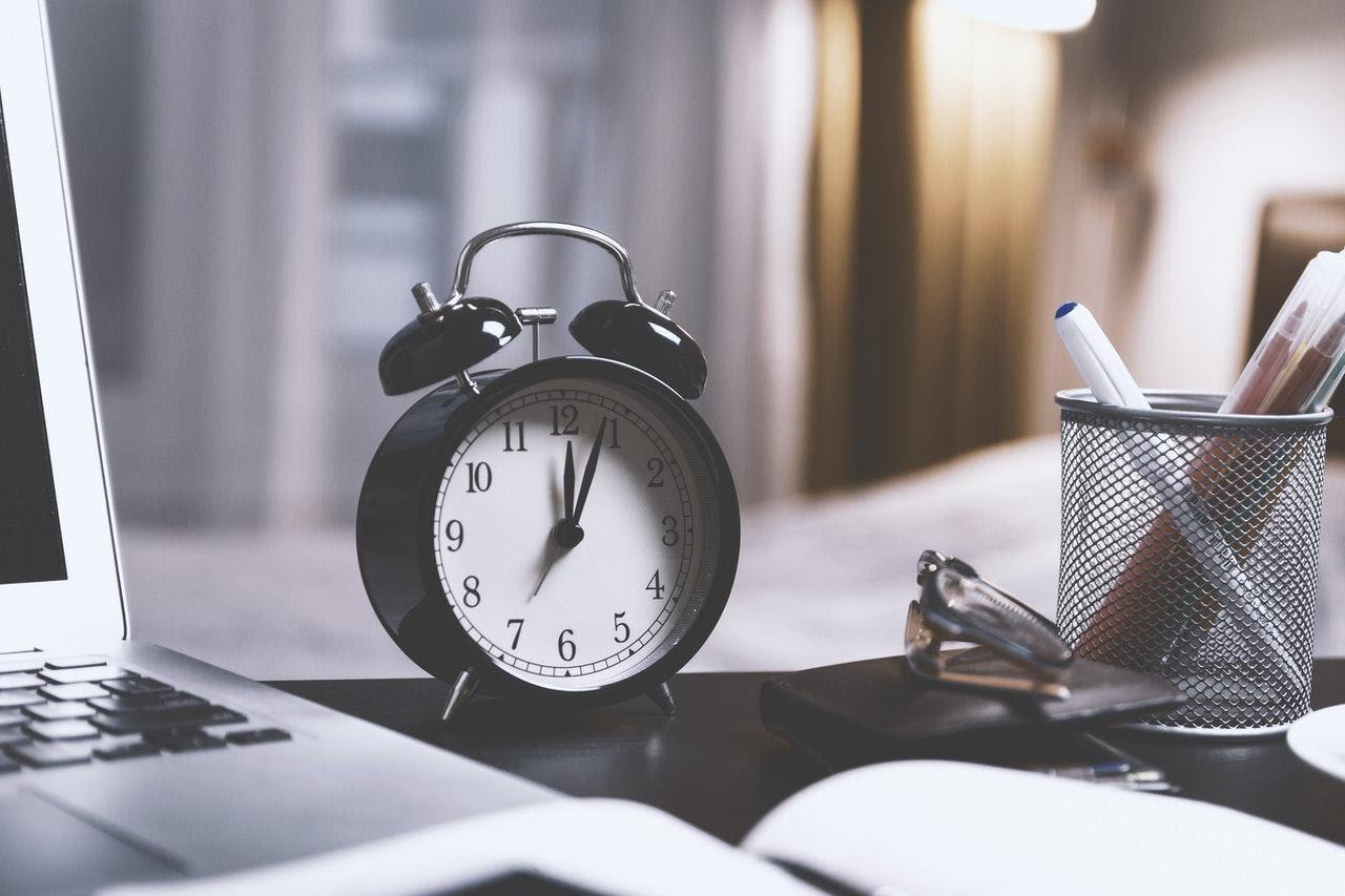 alarm clock on a desk time management strategy