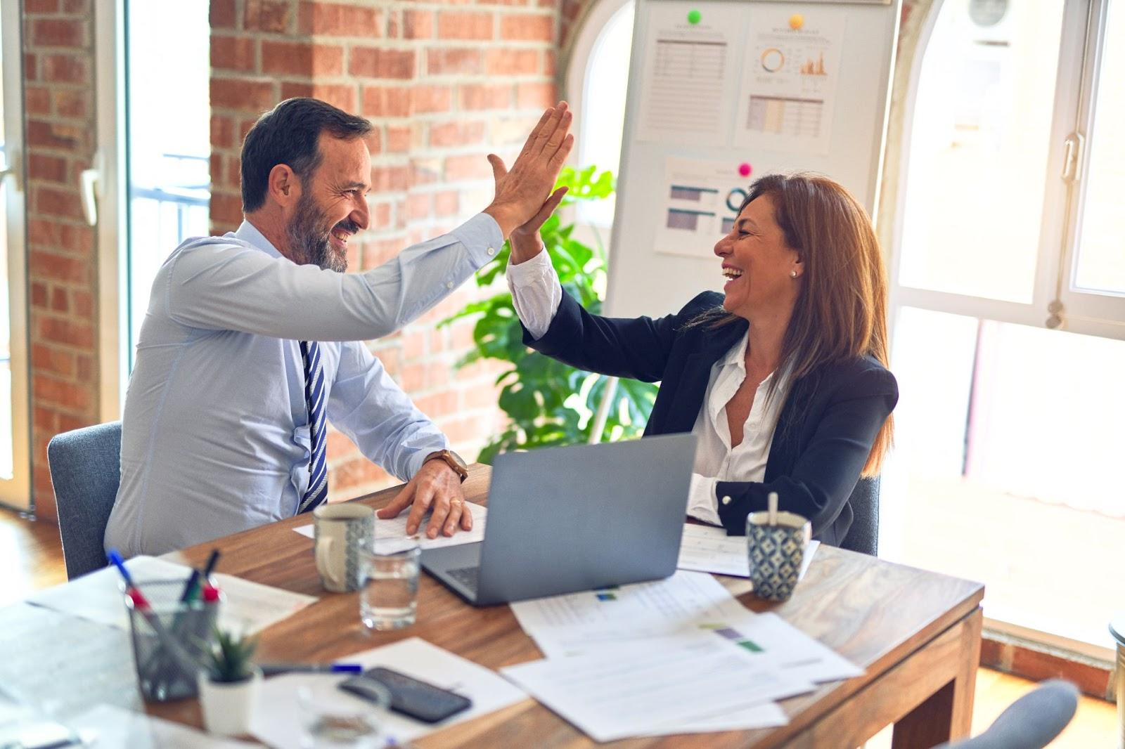high five between male and female employee professional success