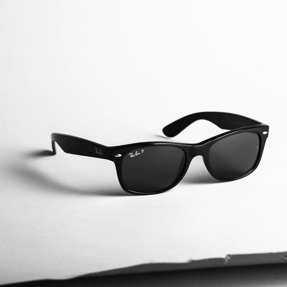 black pair of ray ban sunglasses on white background