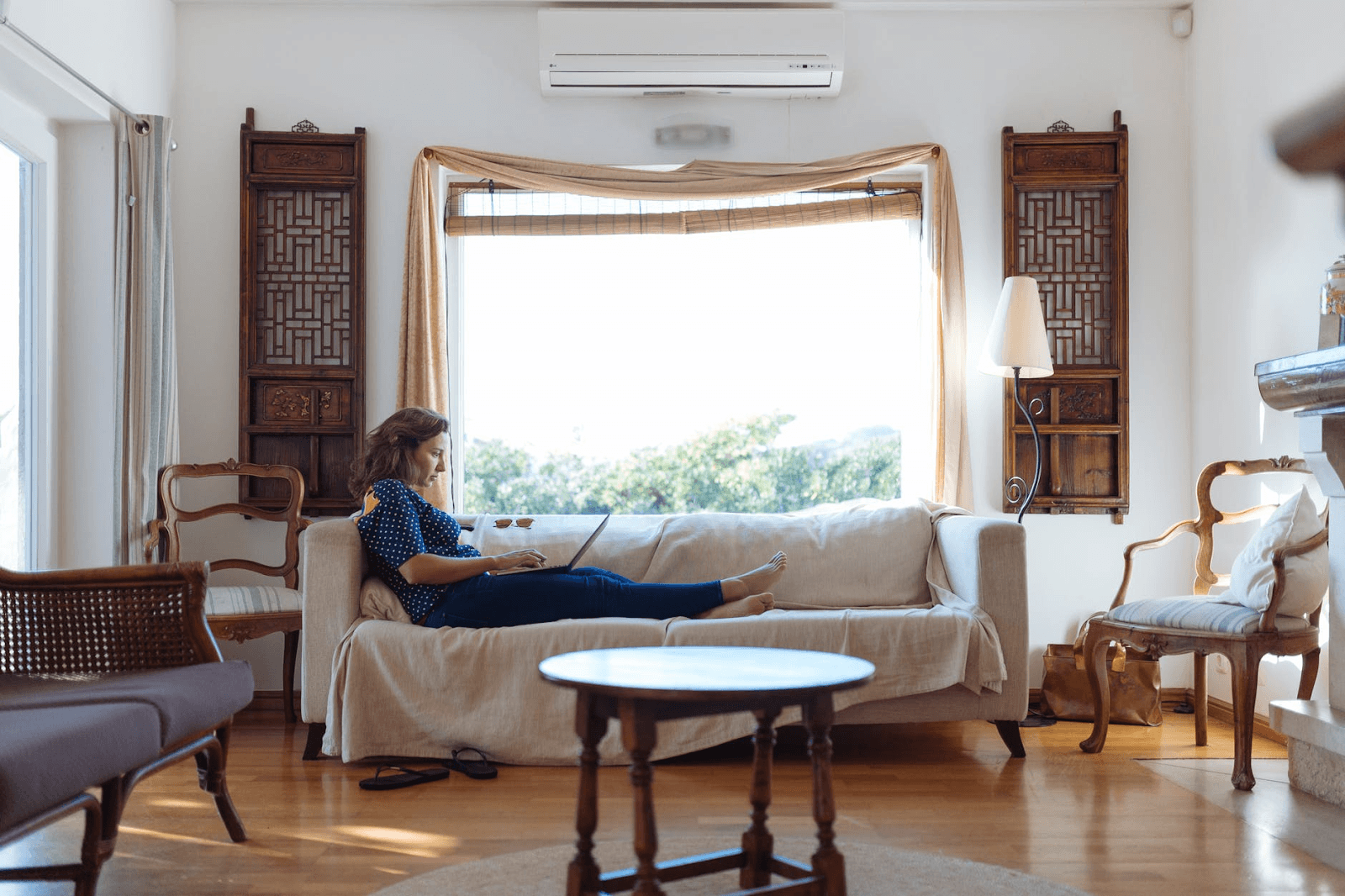 woman-sitting-on-sofa-in-living-room casual working from home