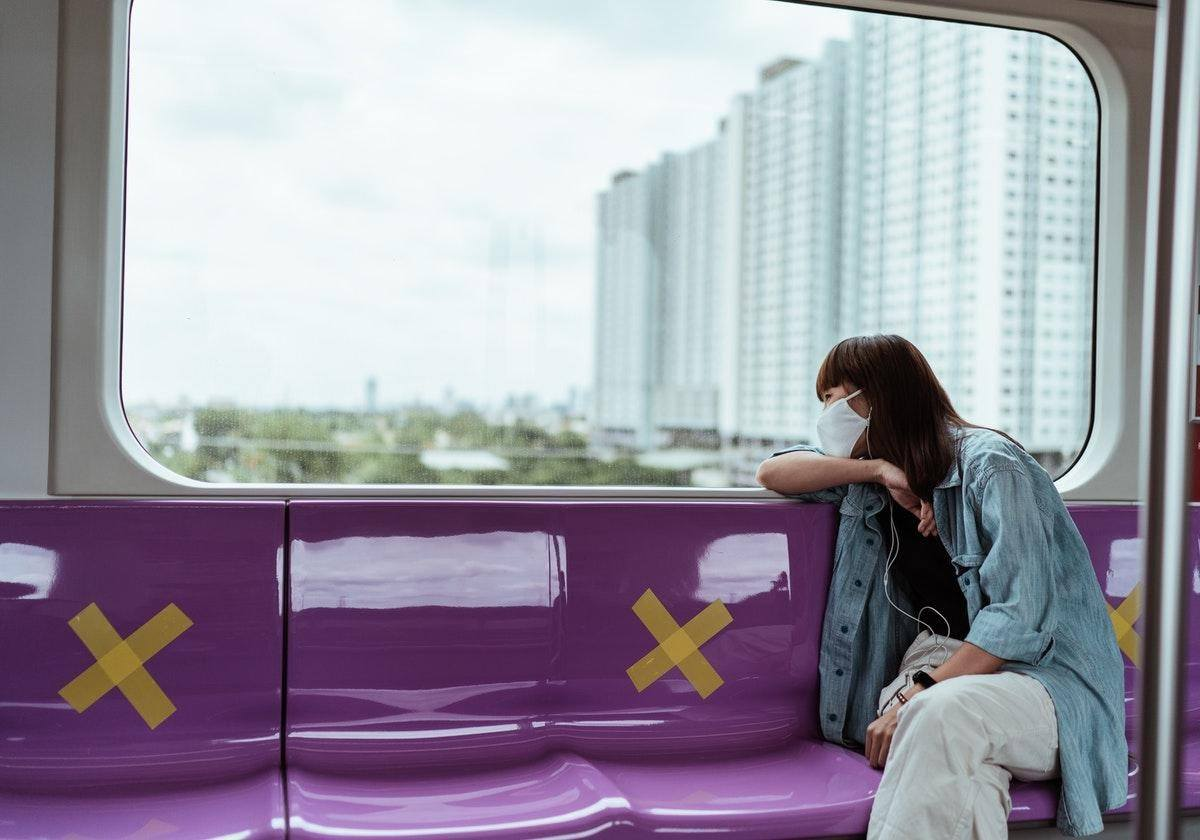 woman looking out train window protecting public transport